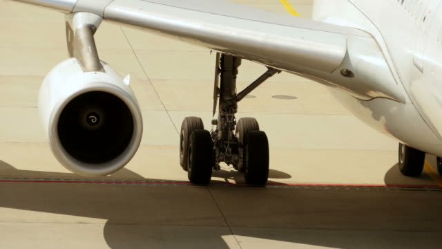 Airport Terminal by Day: Plane Docked at Gate. Landing Gear and Turbine Jet Plane Standing on the Ground at Day. airport runway stock videos & royalty-free footage