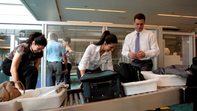 Airport travelers gather belongings after baggage screening video