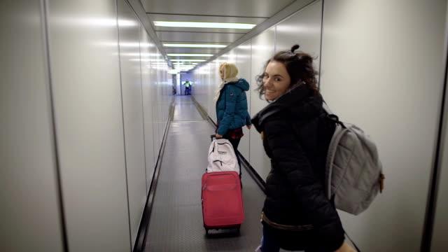 vídeos y material grabado en eventos de stock de aeropuerto. dos mujeres jóvenes en su vuelo. chica rubia con una maleta en una prisa para pasar a través del tubo al plano. morena con una mochila sobre sus hombros en un gran estado de ánimo - abrigo