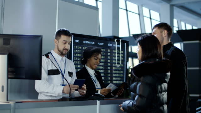 Airport workers checking documents at control point Diverse employees of airport checking passports and biometric data working with passengers. 4K shot on Red cinema camera. customs stock videos & royalty-free footage