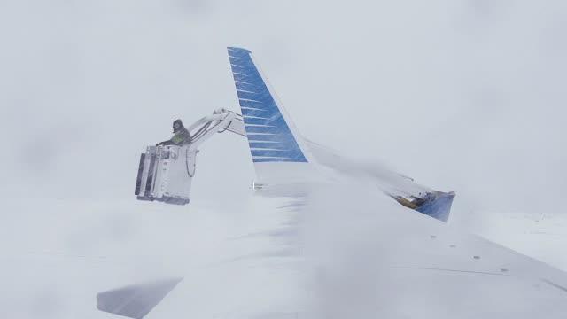 flughafenangestellte vereisten die flügel eines flugzeugs. - zuckerguss stock-videos und b-roll-filmmaterial