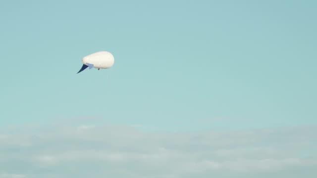 güneş arka plan gri akşam gökyüzü üzerinde gökyüzünde yüzen airships zeppelin gaz helyum çevre gözlemler ve meteorolojik gözlemler yapar - zeplin stok videoları ve detay görüntü çekimi