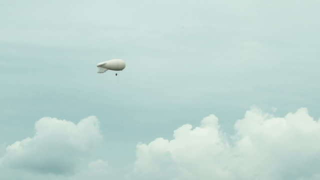 Airships Zeppelin gas helium floating in the sky in sun background on gray evening sky observes the environment and makes meteorological observations video