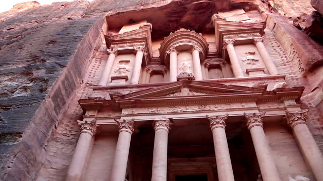 Al Khazneh or the Treasury at ancient Rose City of Petra in Jordan Al Khazneh or Treasury - Nabatean rock-cut temple of Hellenistic period of ancient Petra, originally known to Nabataeans as Raqmu - historical and archaeological city in Hashemite Kingdom of Jordan treasury stock videos & royalty-free footage