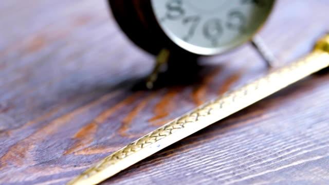 vídeos de stock e filmes b-roll de alarm clock and letter knife - swiss army knife