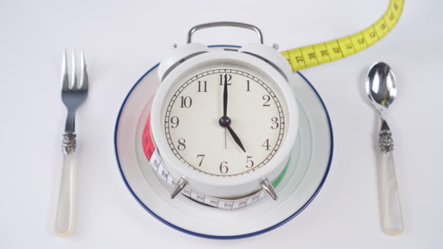 Alarm clock on a white plate with a blue border and a spoon with a fork on the table