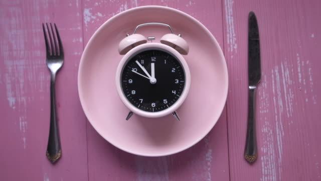 väckarklocka på platt rosa bakgrund - fasta bildbanksvideor och videomaterial från bakom kulisserna