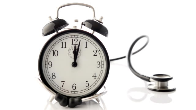Alarm clock ringing surrounded by a stethoscope video