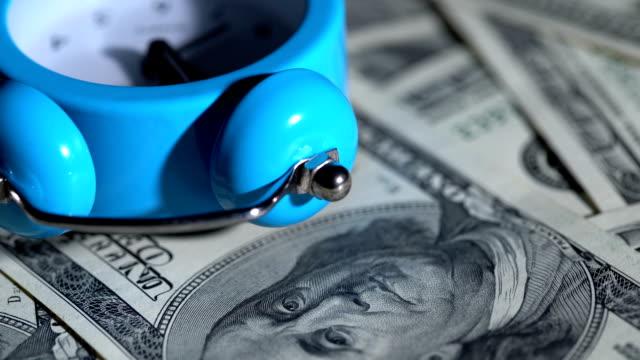wecker dreht sich mit dollarscheinen - inflation stock-videos und b-roll-filmmaterial