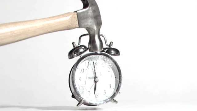 Alarm clock sounds in a super slow motion crushing by a hammer
