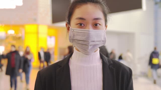 alarmed female traveler wears medical mask china - face mask stock videos & royalty-free footage