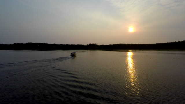 Alaska 4k drone footage tracking past a moving motorboat on the reflective calm Alaskan Moose River with the sunset in the background and boat wake behind. video