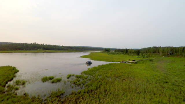 Alaska 4k Drone of calm lazy Moose River on the Kenai peninsula drone tracking shot of boat returning to home dock on a glassy calm Alaskan river with trees in the background. video