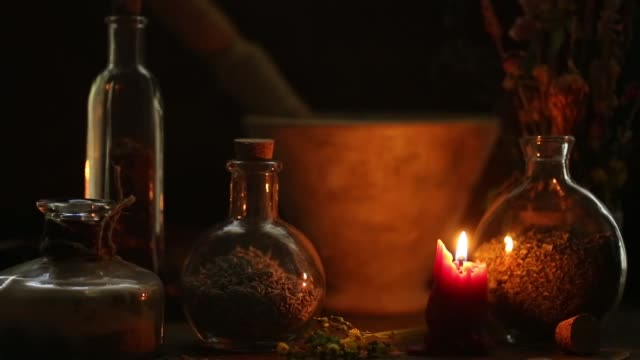 Alchemist Table Candlelight setting of bottles, mortar and pestle and herbs mortar and pestle stock videos & royalty-free footage
