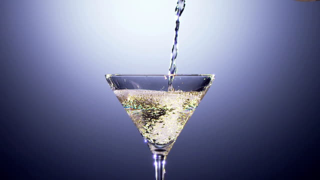 Alcohol beverage is poured into tall martini glass. Slow motion video