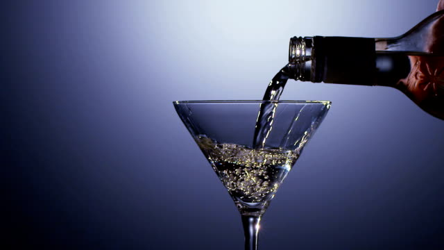 Alcohol drink poured into martini glass of bottle. Slow motion video