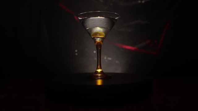 alcohol drink poured into martini glasses of bottle. several glasses of famous cocktail martini, shot at a bar with dark toned foggy background and disco lights. club drink concept. selective focus. slider shot - martini video stock e b–roll