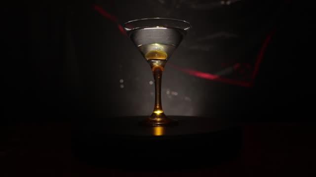 stockvideo's en b-roll-footage met alcohol drinken gegoten in martini glazen fles. enkele glazen van beroemde cocktail martini, schoot in een bar met donker getinte mistige achtergrond en disco lichten. club drankje concept. selectieve aandacht. schuifregelaar schot - martini