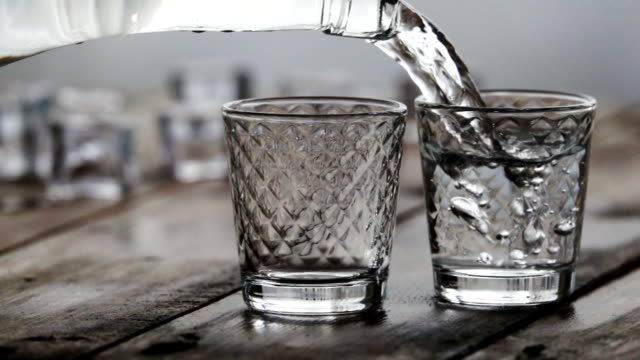 alcohol flow in a glass with ice. vodka pouring - vodka video stock e b–roll