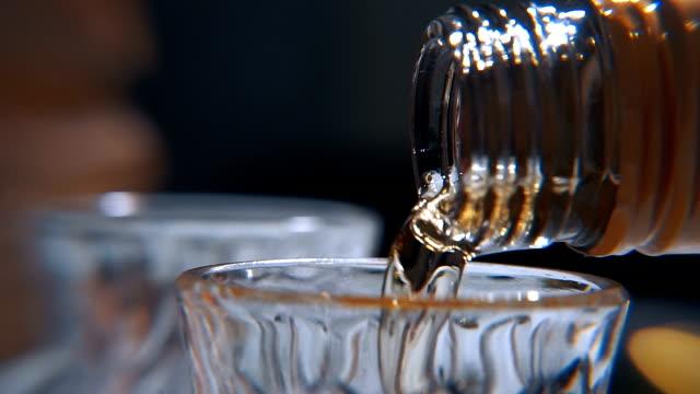 alcool. dalla bottiglia versata in un bicchiere di alcol - rum superalcolico video stock e b–roll