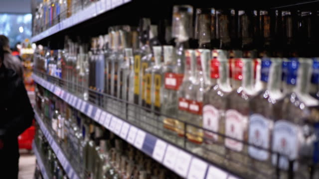 Alcohol Sale in Supermarket. Rows and Shelves of Bottled Alcohol in a Store Window