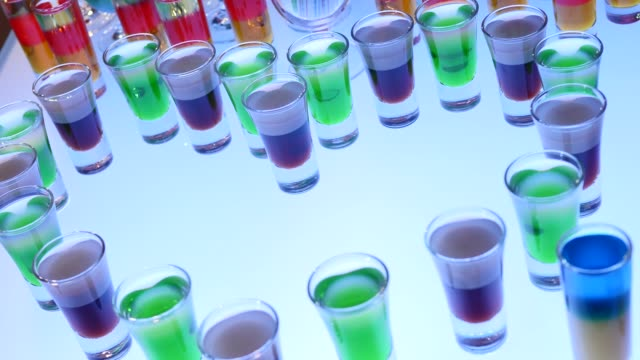 Alcohol vodka in bar nightclub. Shots train falls like dominoes. Party sociable drinking, close up. Colorful pink and blue drinks. Birthday celebration, hen or stag party. Flavored vodka video