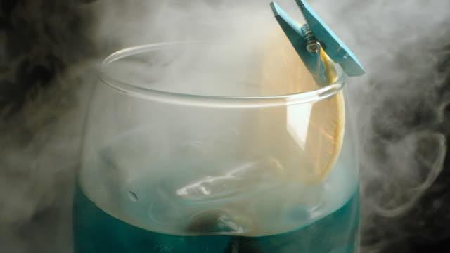 alkoholisches getränk mit zitrone. rauch. nahaufnahme. - tropischer cocktail stock-videos und b-roll-filmmaterial