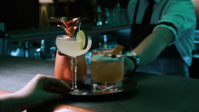 Alcoholic Drinks Are Served At Bar in Restaurant. Shot on Red Epic 4k Uhd Camera. Close-up of Creative Refreshing Drink Mix in Trendy Bar. Concept of Professional Confident Service in Luxury Restaurants Or Waiter Serving. tray stock videos & royalty-free footage