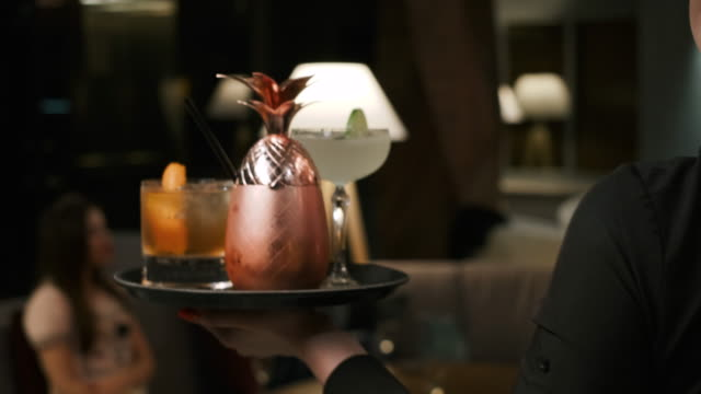Alcoholic Drinks Are Served At Bar in Restaurant. Shot on Red Epic 4k Uhd Camera. Following Shot of Female Waiter Walking with Tray Full of Exotic Cocktails, Serving Them to Company of Young People. Concept of Professional Service in Luxury Restaurants. tray stock videos & royalty-free footage