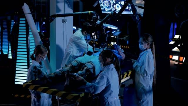 vídeos y material grabado en eventos de stock de alien yace en el laboratorio de la mesa de operaciones. los científicos están experimentando con un humanoide. - autopsia