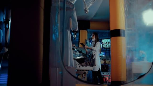 stockvideo's en b-roll-footage met alien ligt op de operatietafel in het laboratorium, aangesloten op een ademhalings-en instrumentatie. vrouwelijke wetenschappers observeren en bijdragen gegevens. zijdelingse overspanning van de camera. - ventilator bed