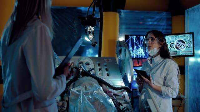 stockvideo's en b-roll-footage met alien ligt op de operatietafel, wetenschappers voeren observaties. de nieuwkomer ligt onder het kunstmatige ademhalingsapparaat, is het duidelijk hoe hij ademt. - ventilator bed