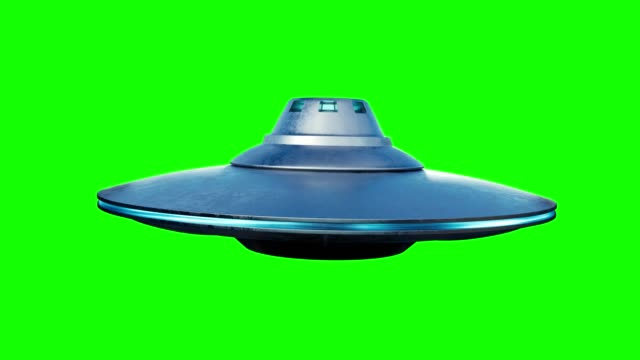 UFO alien spaceship is flying on green background.