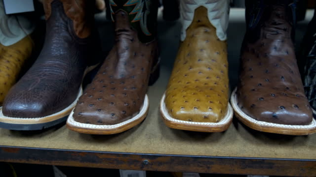 Aligned cowboys boots on a shelf in a store video