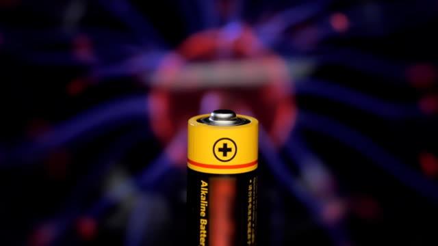 alkaline-batterie dreht sich vor dem hintergrund der plasma-ball - plus stock-videos und b-roll-filmmaterial