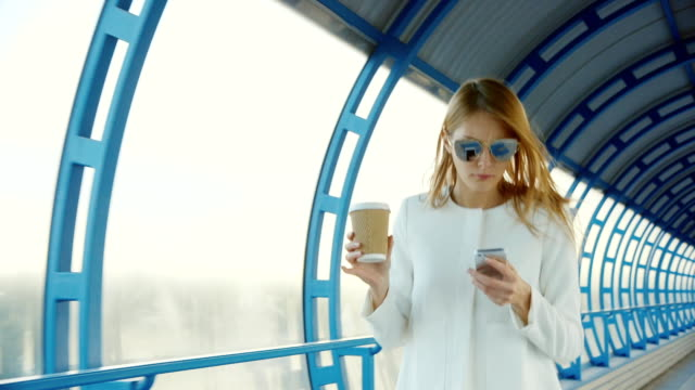 All business on the go. Business woman with a cup of coffee and the phone quickly goes on the tunnel of glass video