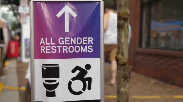 All Gender Restroom Sign at a Gay Pride Festival An all gender restroom sign on a city sidewalk at a gay pride festival. transsexual stock videos & royalty-free footage