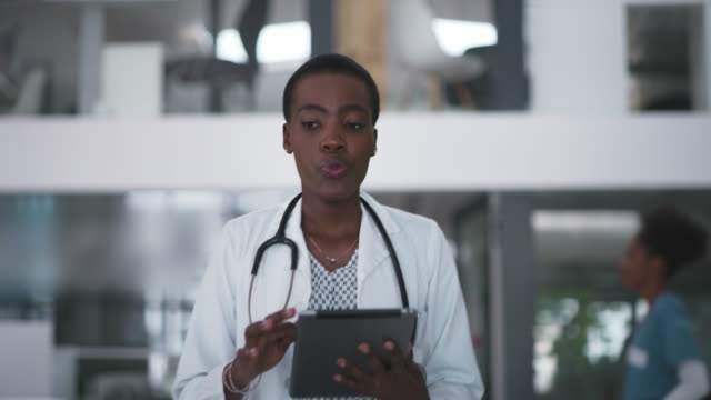 All her patients' files are easily accessible on this awesome tech 4k video footage of an attractive young female doctor using a digital tablet while walking through a hospital female doctor stock videos & royalty-free footage