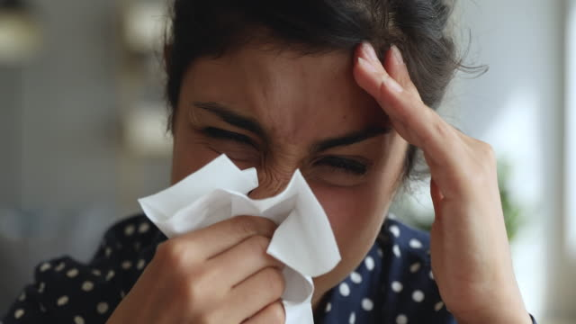 Allergic ill indian woman holding handkerchief blowing running nose Ill allergic upset young indian woman holding tissue blowing running nose in handkerchief got flu fever caught cold influenza symptom at home office, allergy hay fever concept, face close up view flu stock videos & royalty-free footage