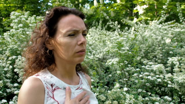 Allergy. Asthma. The woman suffocates at the flowers. video