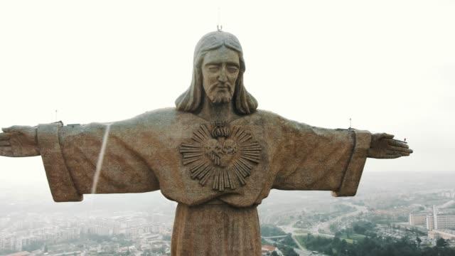 almada jesus stenmonument med öppna armar och sorgligt ansikte - djurarm bildbanksvideor och videomaterial från bakom kulisserna