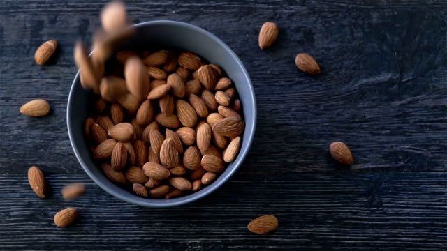 Almond are poured out of it on wooden background Hazelnut Slow Motion Concept. peeled stock videos & royalty-free footage