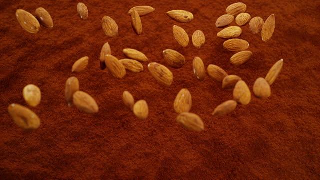 vídeos de stock e filmes b-roll de almonds falling in black chocolate powder, slow motion 4k - amendoas