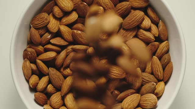SLOW MOTION: Almonds falling into a white bowl - Top View SLOW MOTION: Almonds falling into a white bowl - Top View peeled stock videos & royalty-free footage