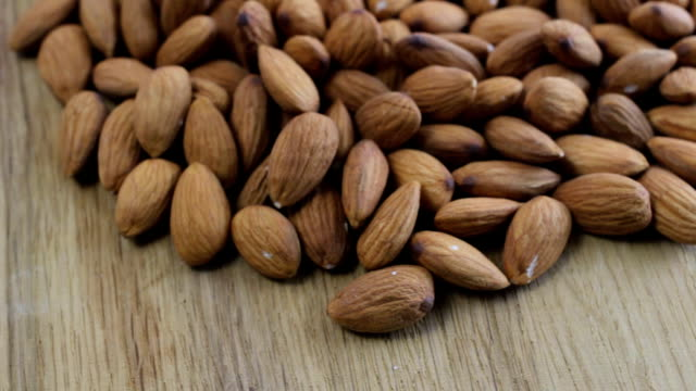Almonds rotating on wooden table close up video