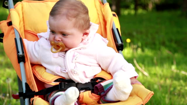 Alone baby sitting in the pram in the park video