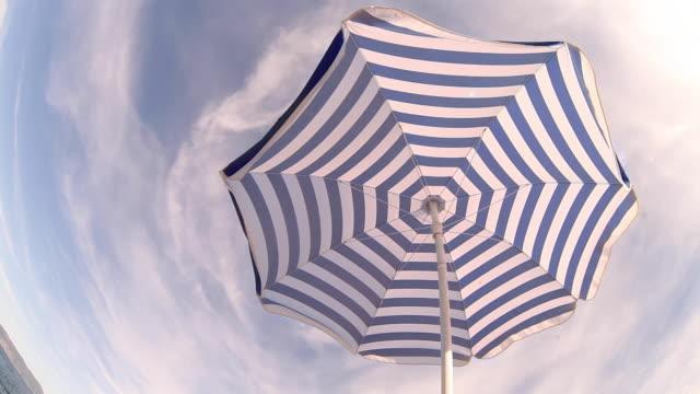 Alone beach retro style umbrella on the croatian shore . Fish eye view.