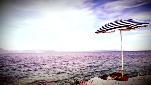 Alone beach retro style umbrella on the mediterranean croatian shore video