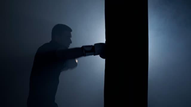 il pugile da solo colpisce il sacco da boxe nella palestra buia. giovane che si allena al chiuso. 4k, uhd - sacco per il pugilato video stock e b–roll