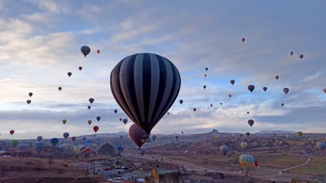 Alone hot air balloon flying low at the snowy landscape of Cappadocia, Turkey Colorful Hot Air Balloon over the snowy landscape of red valley with fairy chimneys at sunrise in winter season in Cappadocia, Turkey hot air balloon stock videos & royalty-free footage